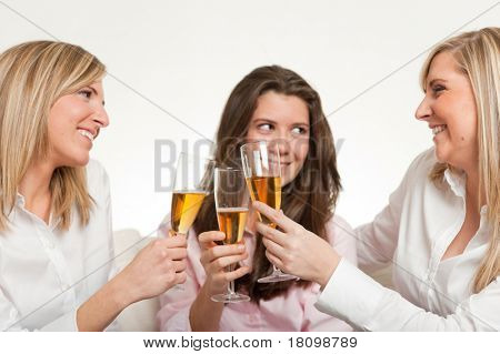Three young female friends toasting with flutes