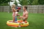 foto of kiddie  - Boys and Girl with Dad in the kiddie pool - JPG