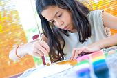 Young girl painting a paper plate with poster paint and wooden brush
