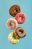 Various decorated doughnuts in motion falling on blue background. Sweet and colourful doughnuts fall poster