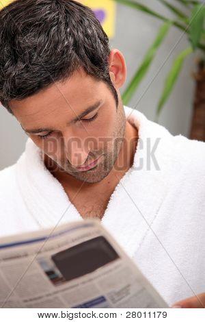 Man reading morning newspaper in kitchen