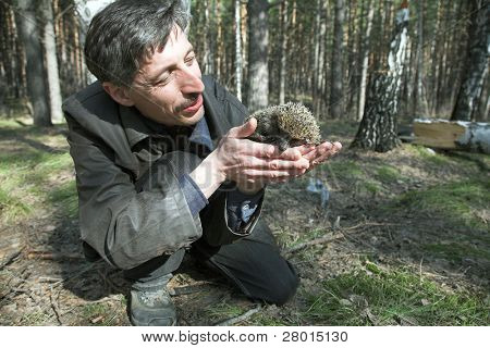 man with little hedgehog in the spring forest