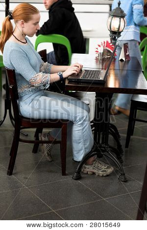 young girl working with computer in the cafe