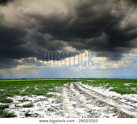 old rural road and dark storm clouds