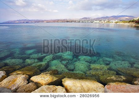 A shallow gulf with the transparent greenish water, surrounded by anchor buoys, in the big southern sea resort