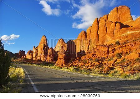 Magnificent road among freakish natural stone formations in the well-known park in the USA arch