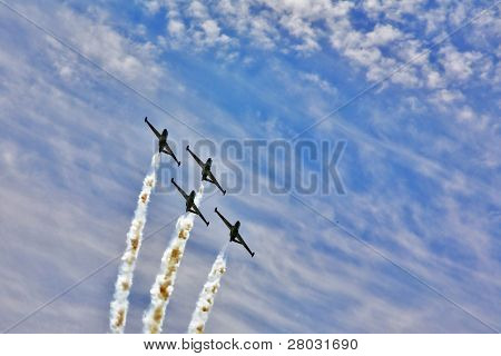 Synchronous  flight of four sparkling planes on air parade