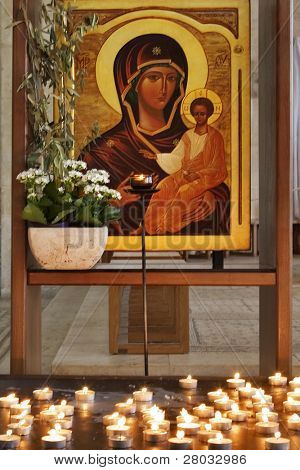 An icon of the Virgin with the baby and a burning candle before it(her)