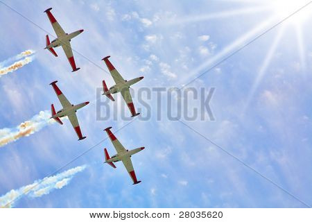 Synchronous flight in beams of the sun of four sparkling planes on air celebratory parade