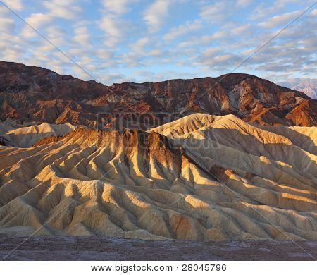 Sunset. The famous section of Death Valley in California - Zabriskie Point. Picturesque hills of pink, yellow and chocolate hues