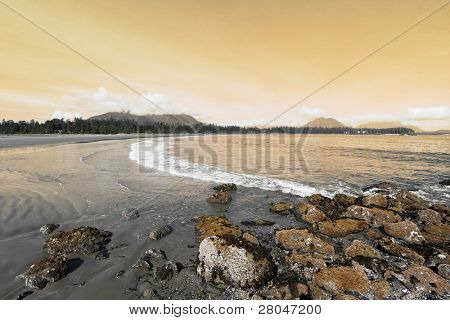 Vancouver Island, sunset. On the Pacific beach begins tide, wet sand, and puddles