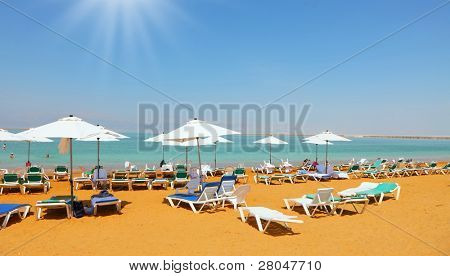 Sunny spring day on the beach luxury hotel on the Dead Sea in Israel. A few swimmers in the water, take the sea baths