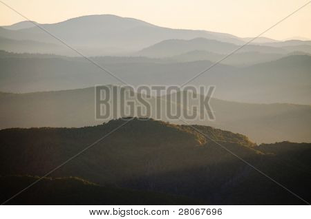 mountains at sunrise in fog
