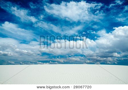 dynamic clouds over white sand dunes