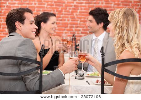 Friends raising their glasses in a toast at a restaurant