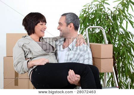 Man  carrying his partner over the threshold of their new home