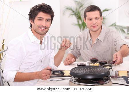Men eating raclette