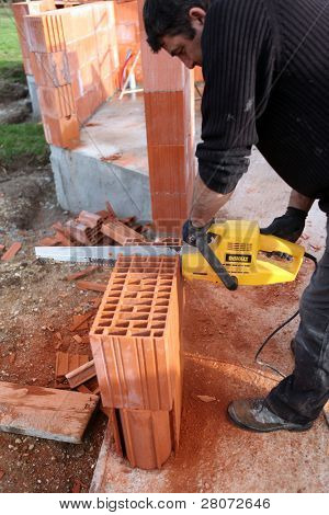 Man using a chainsaw to cut through a brick