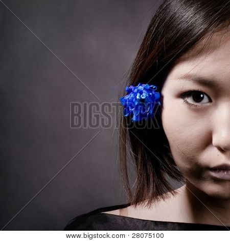 half face portrait of asian woman with blue flower