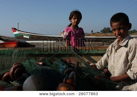 GOKARNA, INDIA - DECEMBER 14: The son of a fisherman from Indian state Karnataka, help prepares gear for fishing in the Indian ocean, December 14, 2008 in Gokarna, India.
