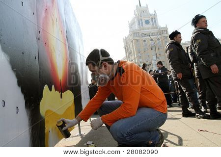 MOSCOW - MARCH 31: A man sprays paints during â??Generation Against Terrorâ? anti-terror demonstration at Triumphal Square on March 31, 2010 in Moscow.