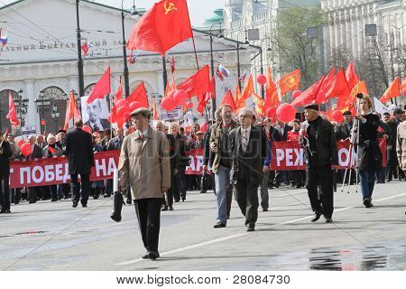 MOSCOW - MAY 1: Communist party supporters take part in a rally marking the May Day, a portrait of the Soviet founder Vladimir Lenin seen in the background, May 1, 2010 in Moscow, Russia.