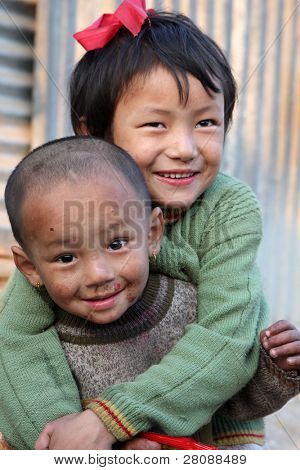 KATHMANDU, NEPAL - JANUARY 7: children  Di Lakshmi (back) and Vishnu Kumar of a poor area at Old Baneshwor near Bagmati river, January 7, 2009 in Kathmandu Nepal.