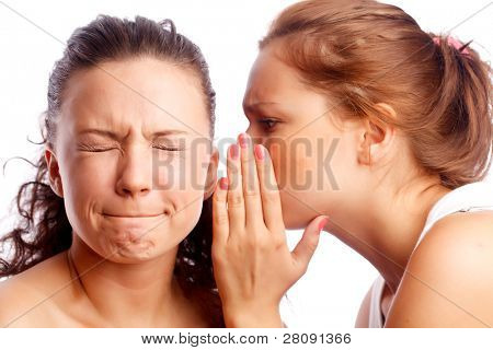 Young woman whispering something to her friend.