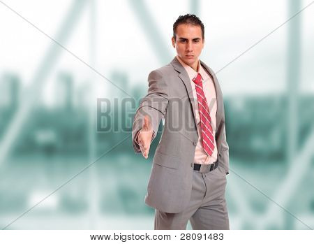 Closeup of a young business man thumb up standing in a light and modern business hall.