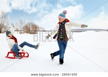 Portrait of happy couple in warm clothes tobogganing in winter