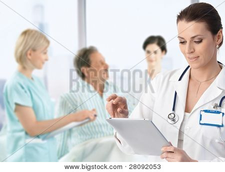 Doctor recording information to electronic tablet at patients bed, team working in background.?