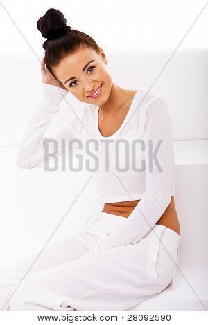 Smiling elegant lady with neat chignon on top of her head dressed in white on white sofa, health and well-being concept.