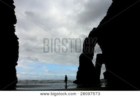 elephant stone and a woman in silhouette at Las Catedrales, Galicia north of spain