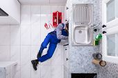 Young Male Plumber Repairing Sink Pipe With Adjustable Wrench poster