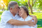 Portrait Romantic Older Couple. Attractive Handsome Older Husband Embracing And Kissing His Older Wi poster