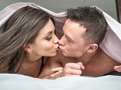 Handsome Kissing Couple Under A Duvet In The Bed. Happy Young Couple Lying Down Comfortably In Their poster
