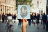 Hand Holding A Paper Sheet With Fingerprint Icon Over A Crowded Street Background. Concept Of Social poster