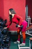Athletic Sports Girl In Red Leggins Trains In The Gym. Woman Lifts A Dumbbell. Sports Fitness And We poster
