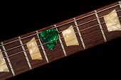 Green Guitar Pick On The Fingerboard And Dark poster