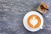 Top View Of Hot Coffee With Heart Pattern In White Cup And Brown Sugar On Stone Table Background. A  poster