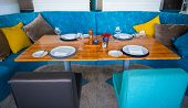 Modern Blue Dining Room, There Are Chairs And Table Setup With Fancy Items. Elegant Table Set In Mod poster