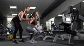Portrait Of Two Young Sportive People Doing Exercises And Training In Gym. Beautiful Brunette Lookin poster