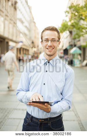 Homem com o computador da tabuleta na rua