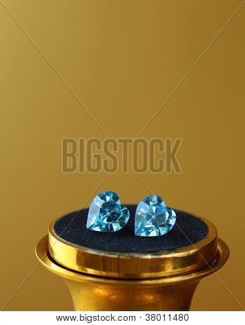 Pair of earrings topaz jewelry stud , macro shot on gold background