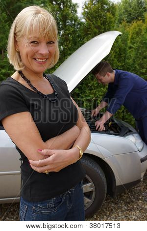 Mature Female Motorist Getting Her Car Fixed By Mechanic