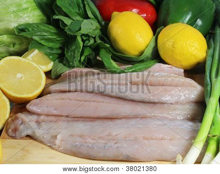 Fresh fish fillets with lemons and basil