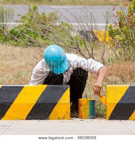 Man Painting Roadworks Barriers On A Road In Vietnam