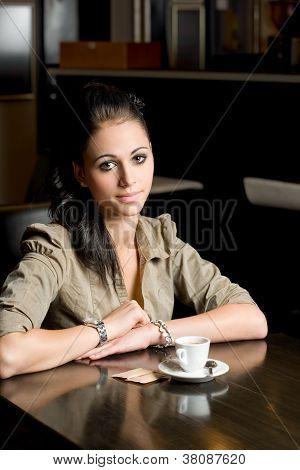 Morena sola en una cafetería.
