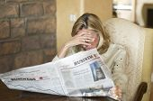 pic of stock market crash  - Mature woman reading the financial newspaper and being depressed - JPG