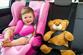 stock photo of baby bear  - baby girl with his teddy bear smile in car - JPG